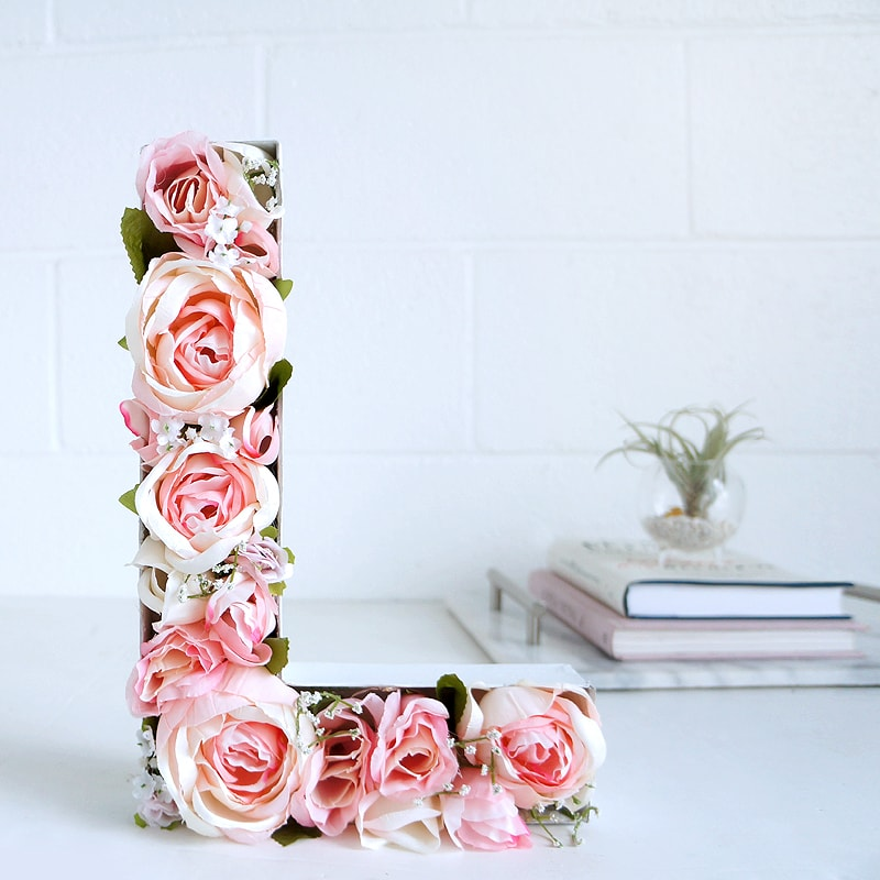 Photo of a flower letter in front of a stack of books and a succulent.