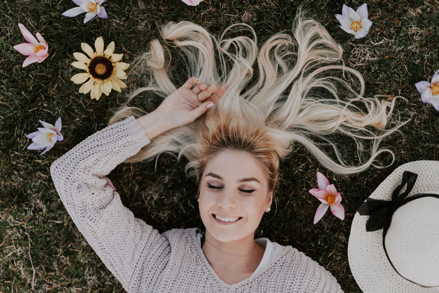 Blonde girl sitting in grass with hair laid out, flowers, and a hat