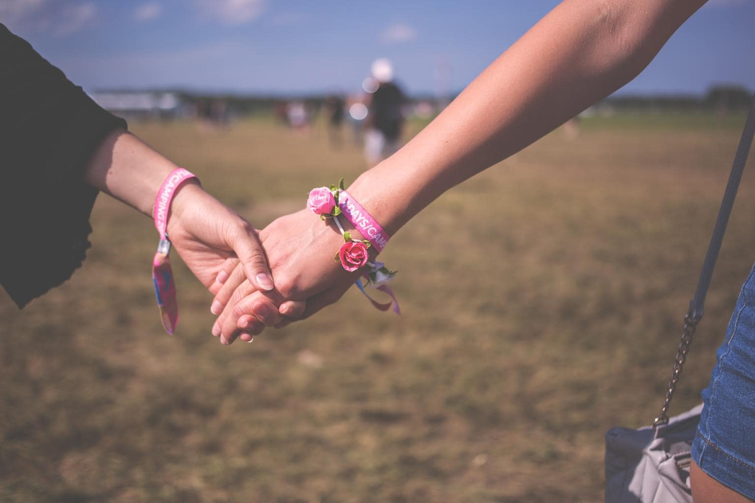 Girls holding hands and wearing friendship bracelets at a music festival