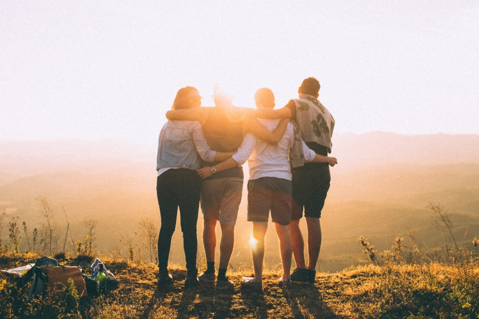 Friends hugging as sun sets on mountain top