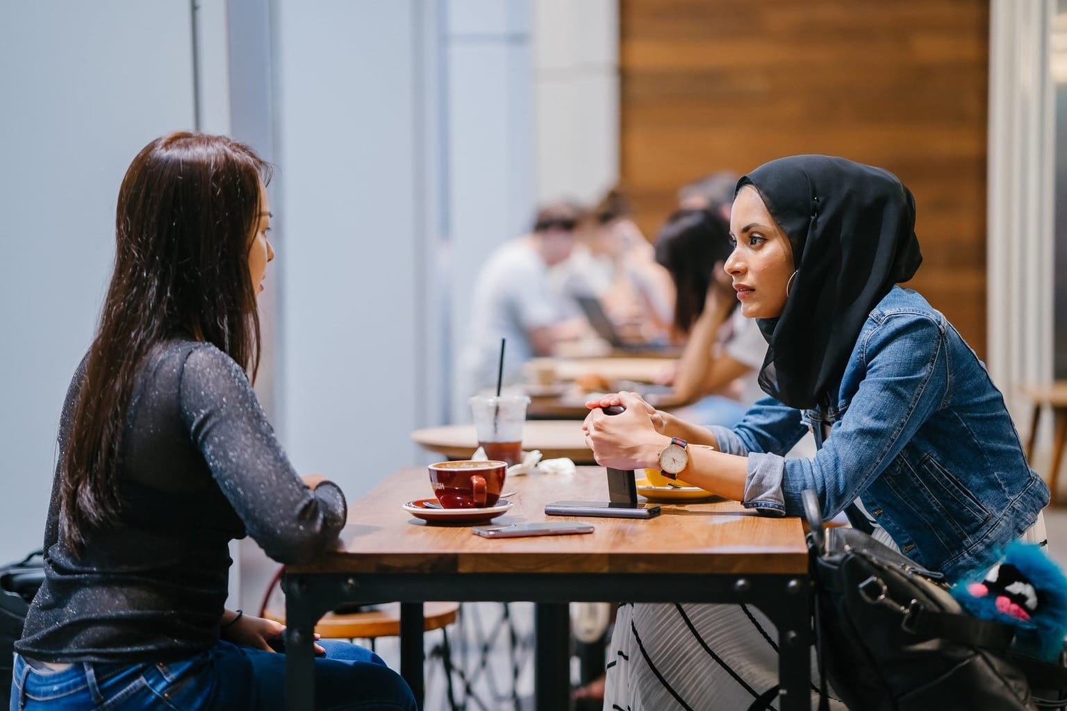 Two friends sitting at a table with coffee talking