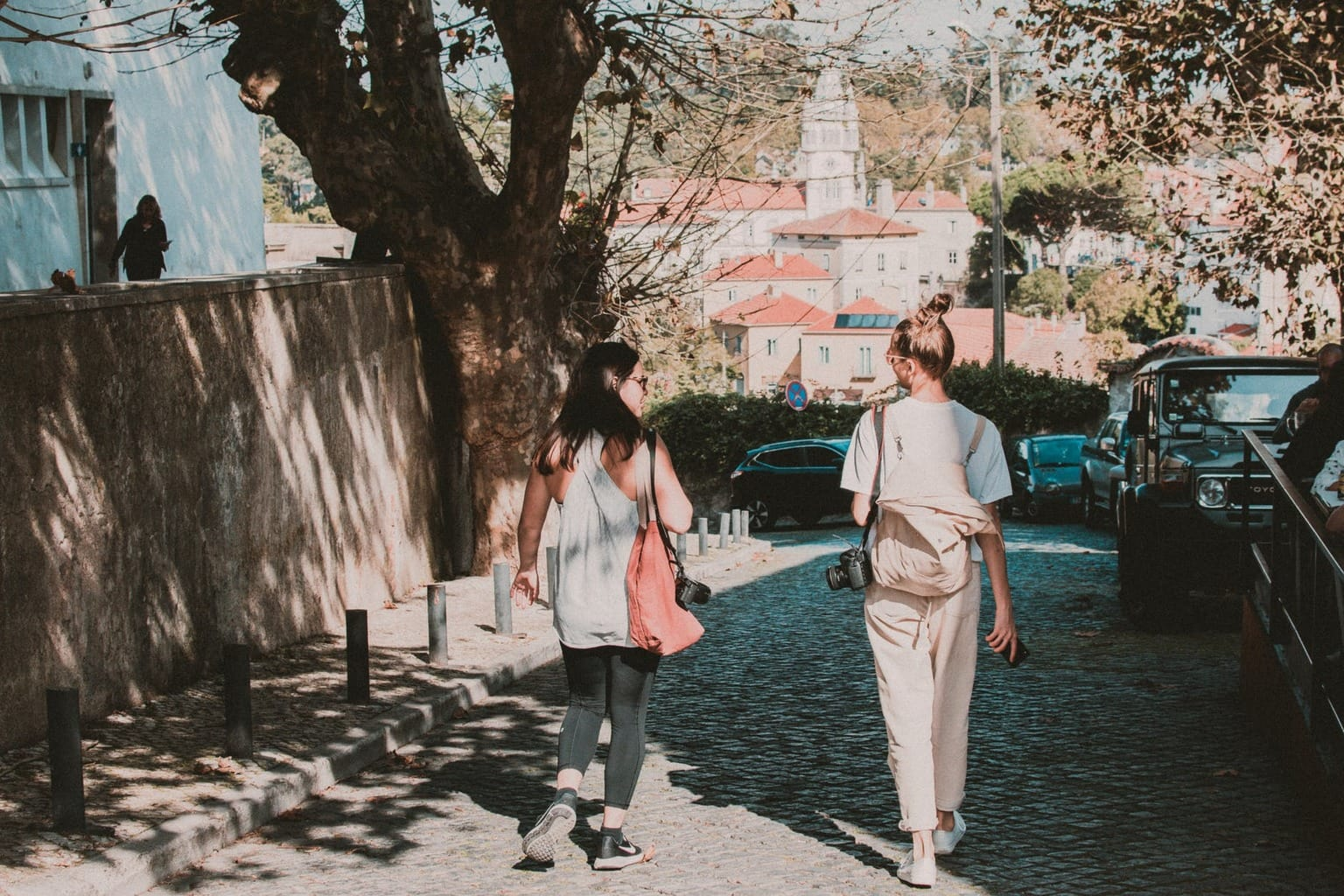Two girls walking down the street with bags