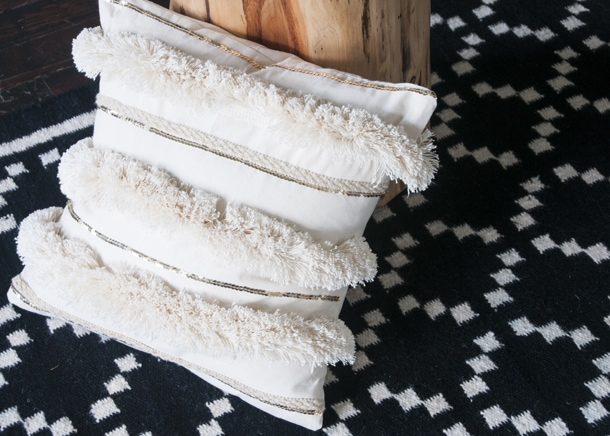 Photo including a fringe pillow leaning against a wooden table sitting on a geometric rug.