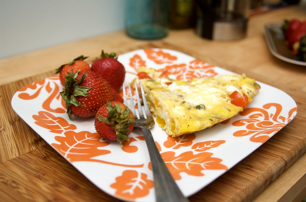 A slice of frittata on a plate with strawberries and a fork