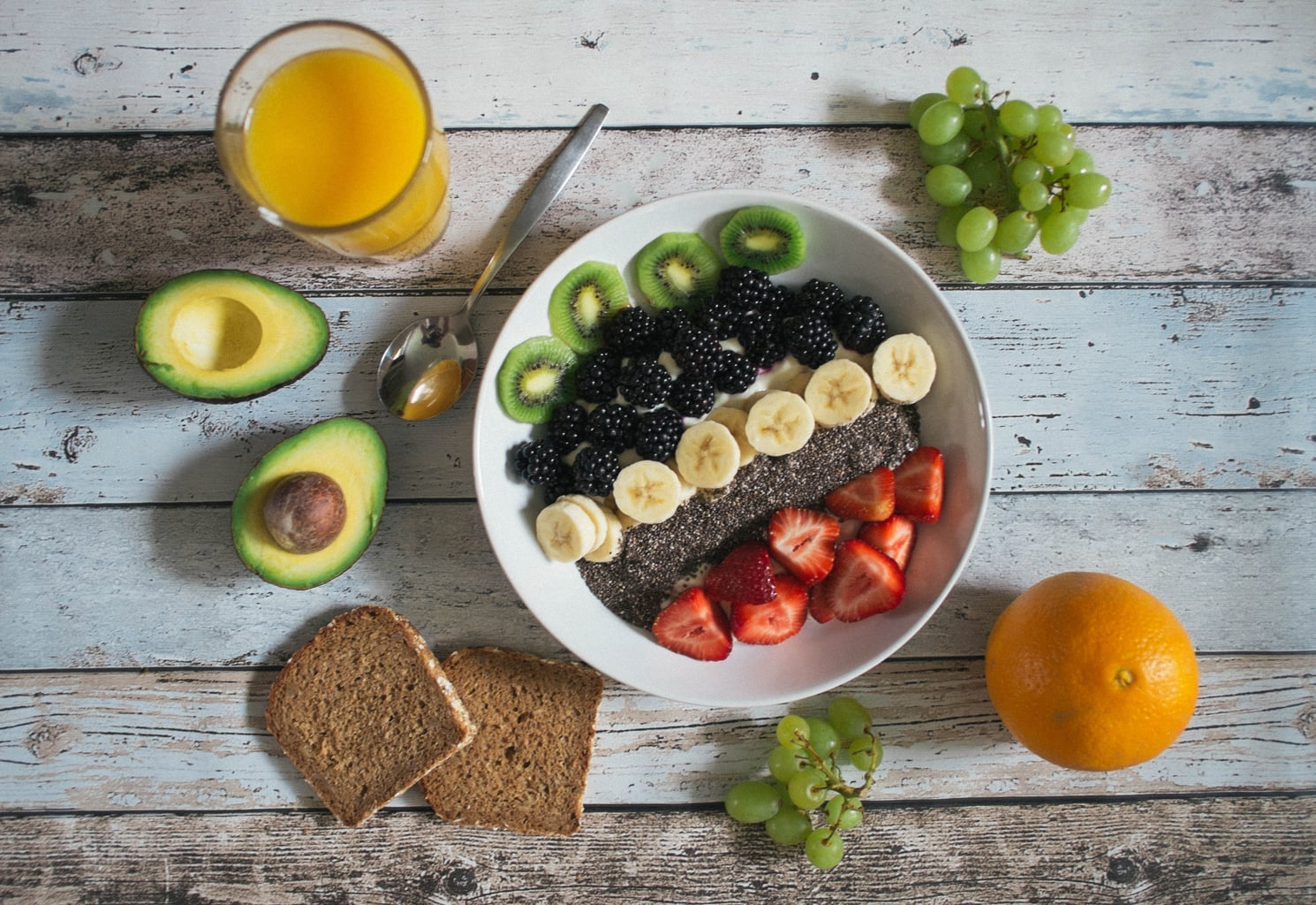 variety of fruits (kiwi, grapes, avocado, orange banana, strawberry) in a bowl with orange juice and bread on a wooden table