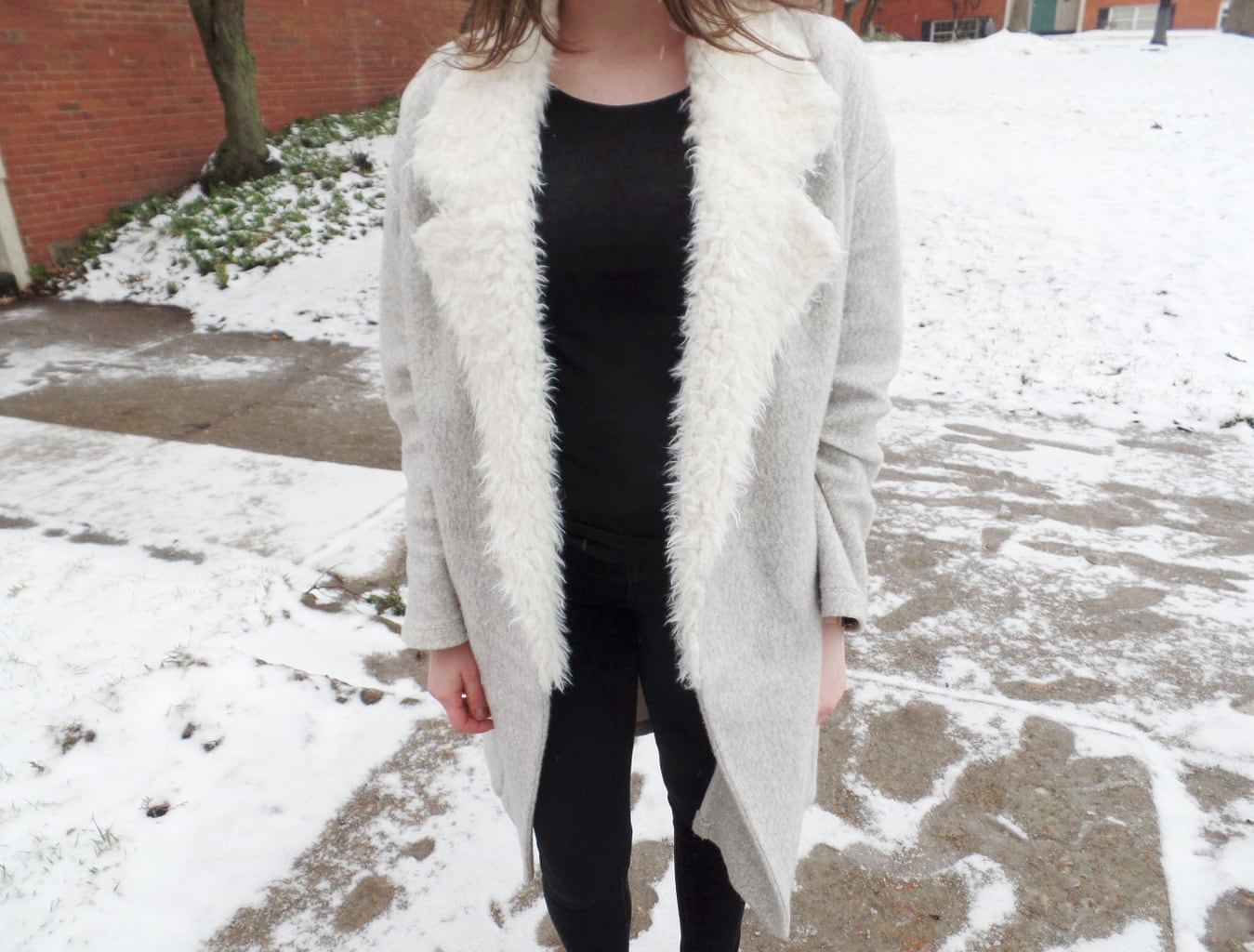 Mercyhurst University student Chloe wears a light grey longline coat with white fur lapels with her all black outfit.