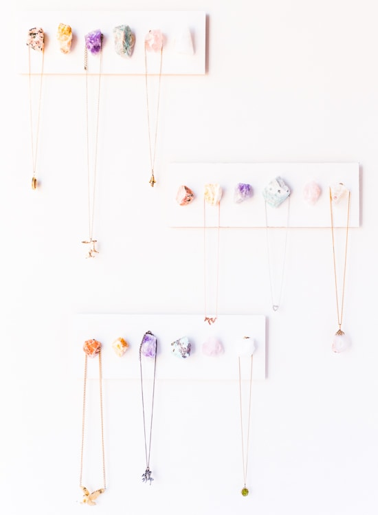 Photo set of three geode/crystal jewelry holders with necklaces hanging off of them.