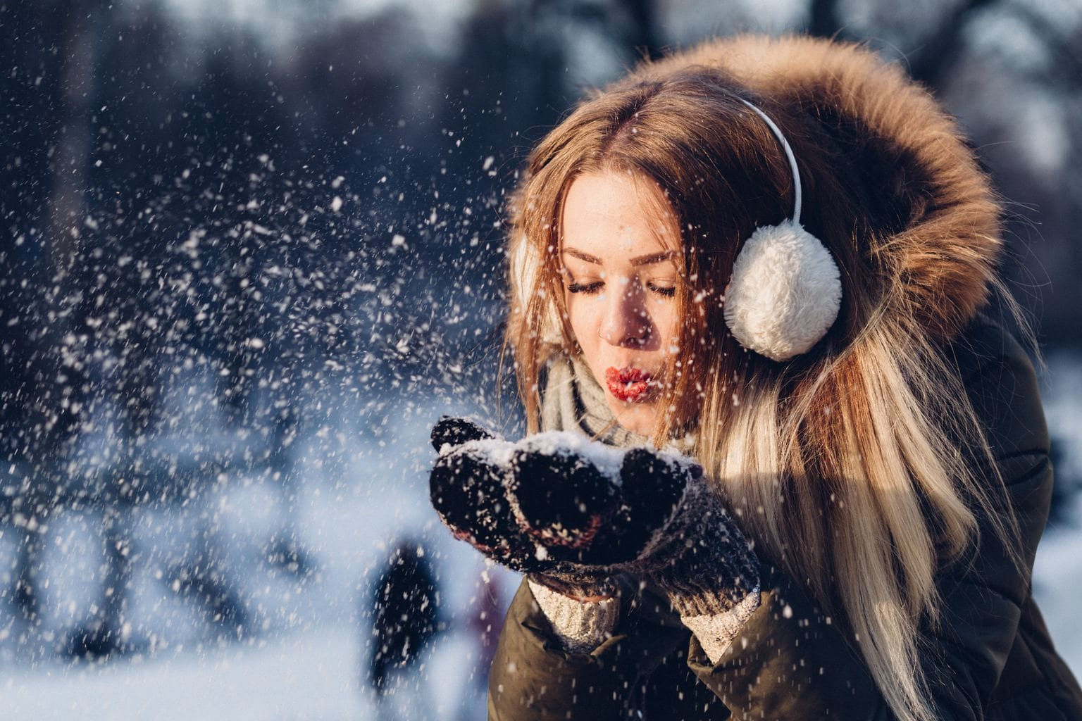 Girl with earmuffs blowing snow in the wintertime.