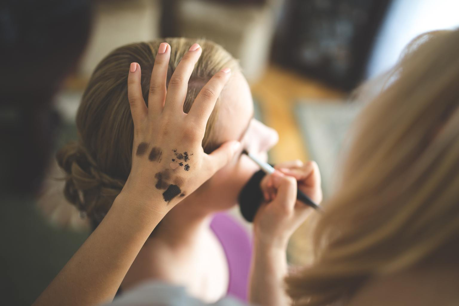 Women doing eyebrow makeup.