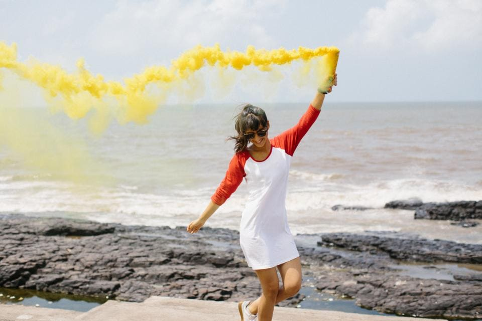 Photo of girl running with yellow chalk dust in her left hand. She's next to the beach and wearing a red and white henley dress and white sneakers.
