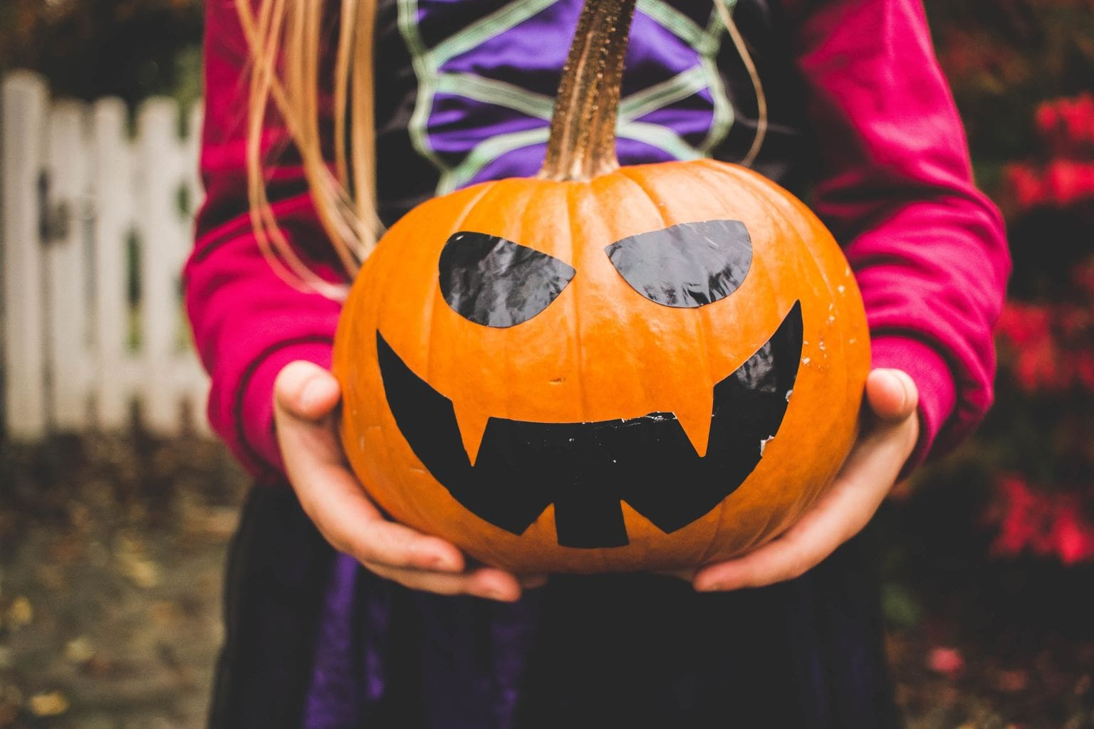 Halloween makeup: Photo of a girl holding a pumpkin painted with a jack o lantern face