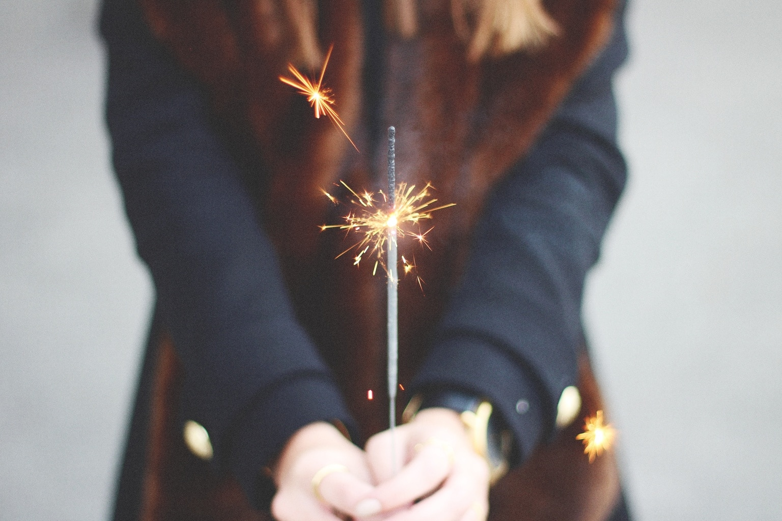 Girl holding a lit sparkler in her hands