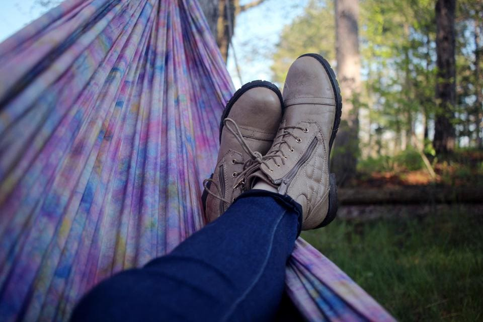 Girl relaxing with boots in a hammock