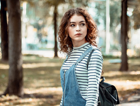 Girl in a striped shirt and overalls taking a walk in the woods