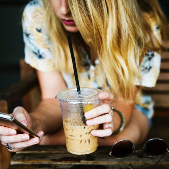 Girl using social media on her phone while holding a coffee