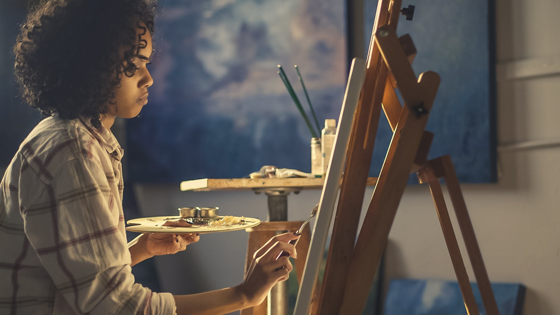 Girl in white shirt painting on an easel with blue painting in background