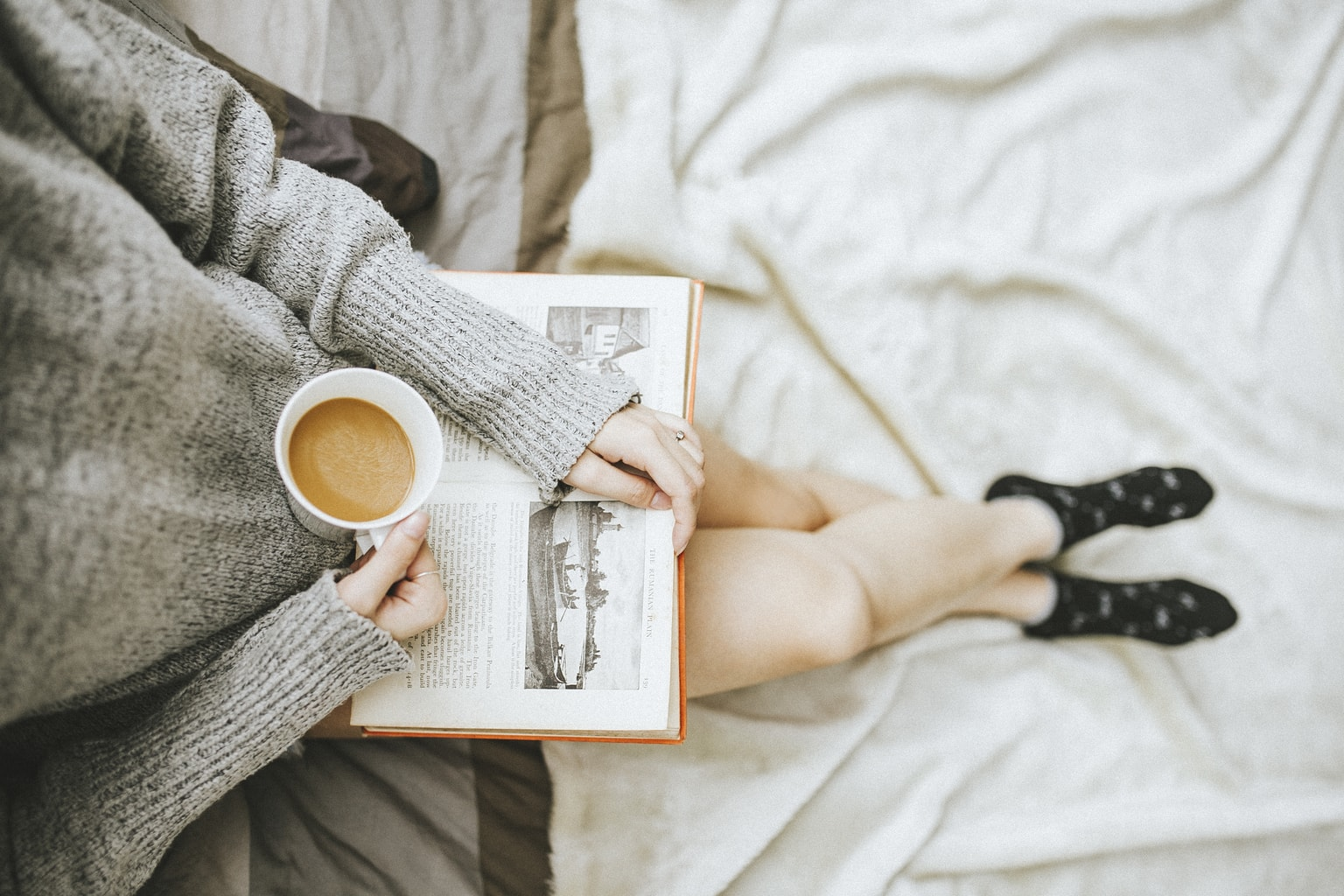 Photo of girl wearing a gray sweater and black patterned socks reading a book and drinking coffee.