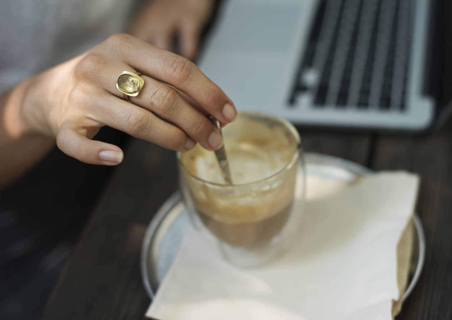 Girl stirring her coffee while working on a laptop