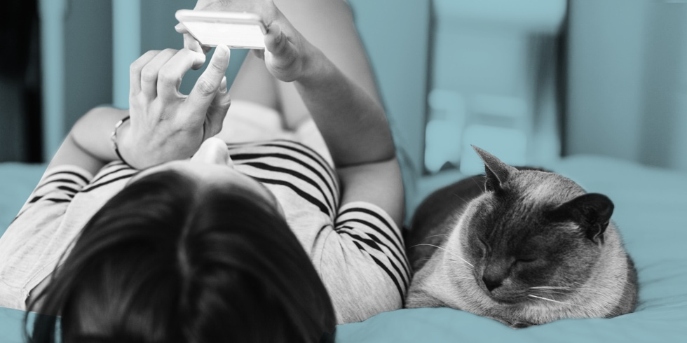 girl-texting-beside-cat