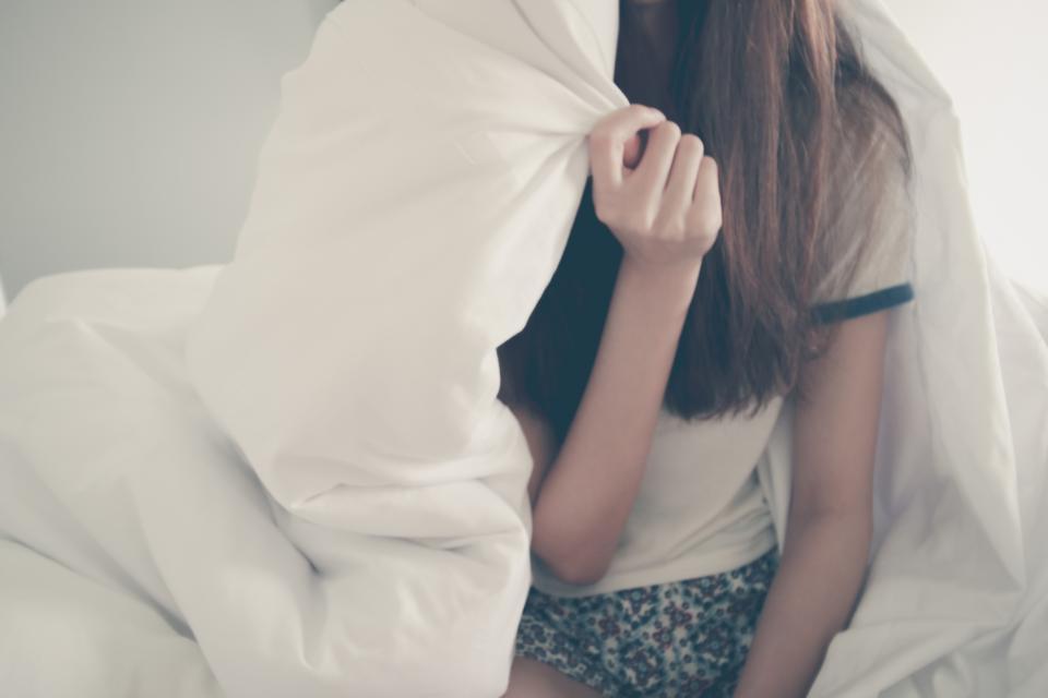 Girl under white comforter in bed