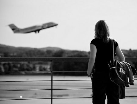 Girl watching airplaine take off