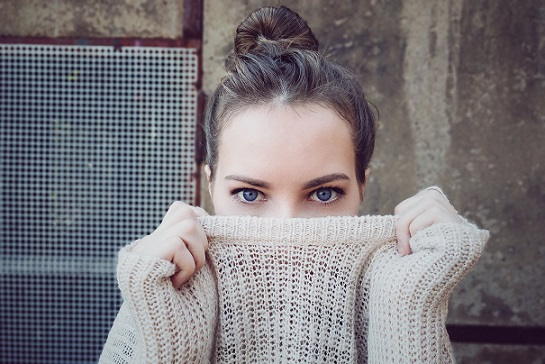 Girl with Bun Hiding Behind Her Sweater
