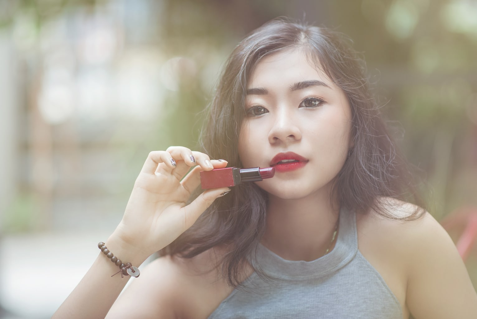 Girl holding a lipstick up to her mouth: Day to night makeup guide for students