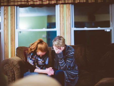 Two girls crying on a couch at night