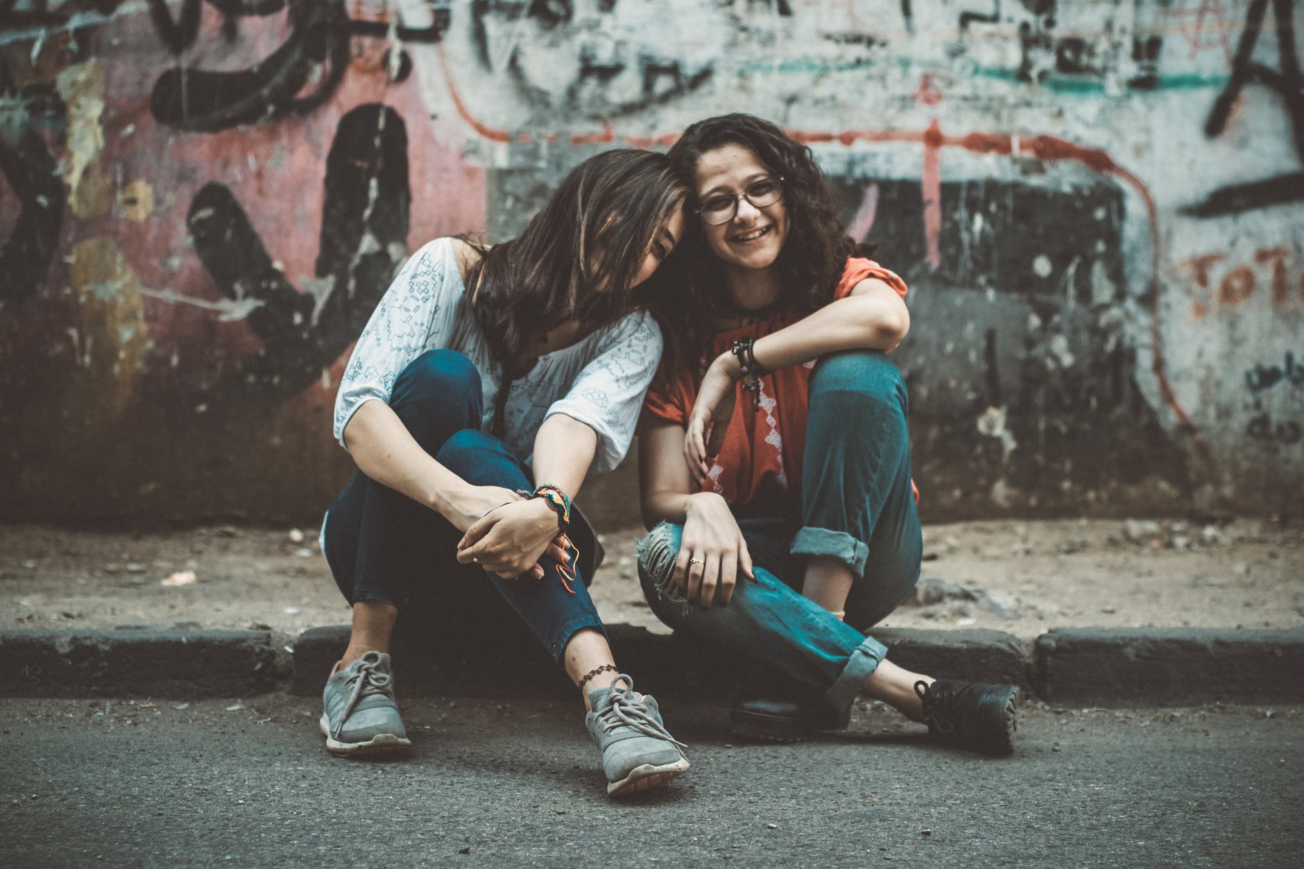 Two girls sitting on the street with graffiti laughing