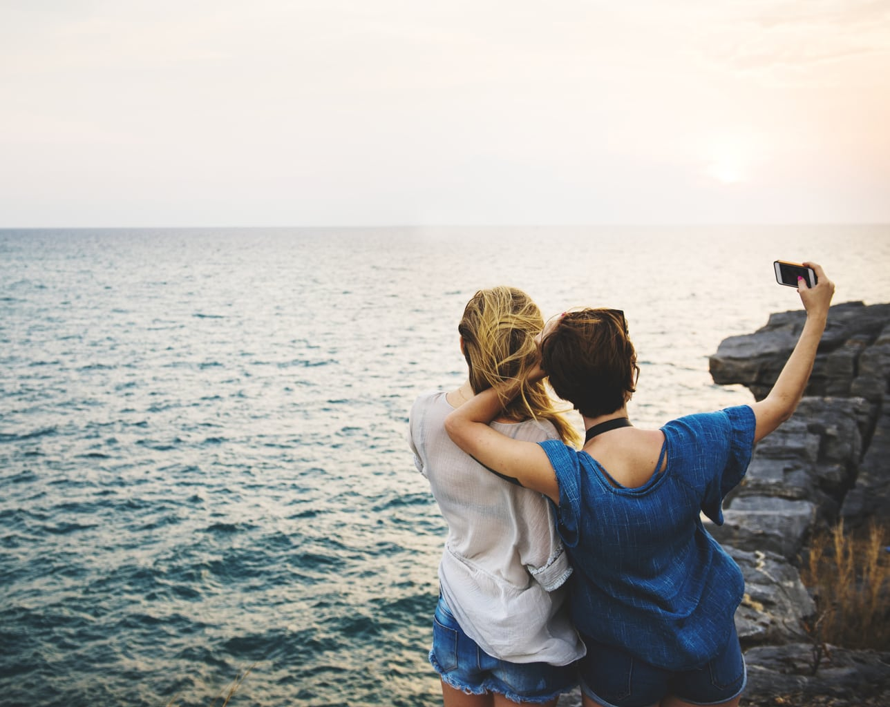 Photo of a blonde and brunette girl taking a photo on the edge of a cliff.