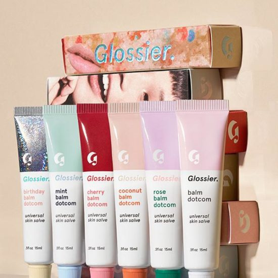 Photo of all Glossier Balm Dotcom flavors (Birthday Balm Dotcom, Mint Balm Dotcom, Cherry Balm Dotcom, Coconut Balm Dotcom, Rose balm Dotcom, Original Balm Dotcom) in front of boxes of the product stacked up on a beige surface against a beige background