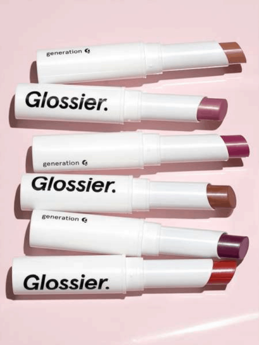 Tubes of Glossier Generation G lip color laid down against a glossy pale pink background, in the shades (from top to bottom): Cake,