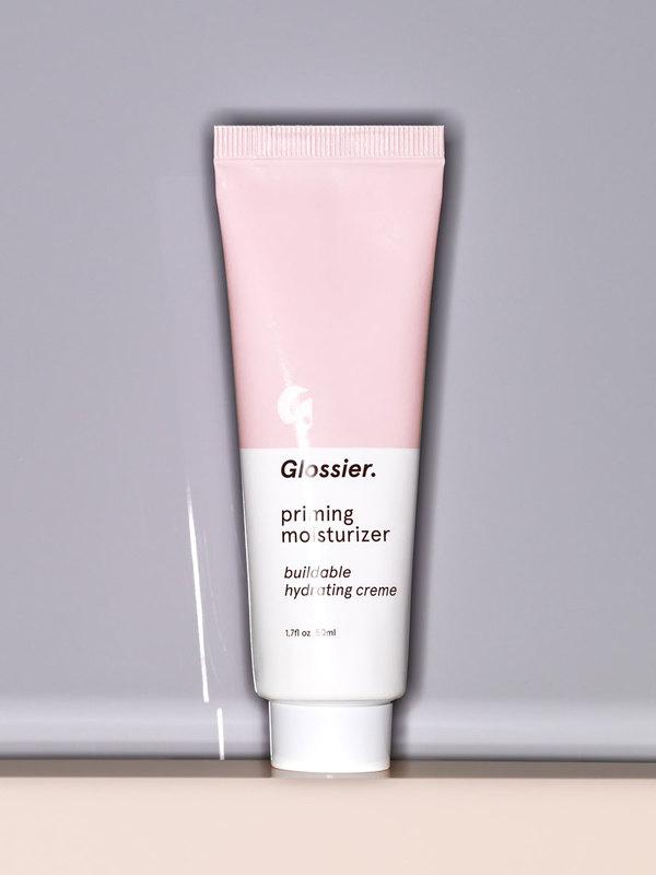 Photo of Glossier Priming Moisturizer resting on a beige surface against a gray background