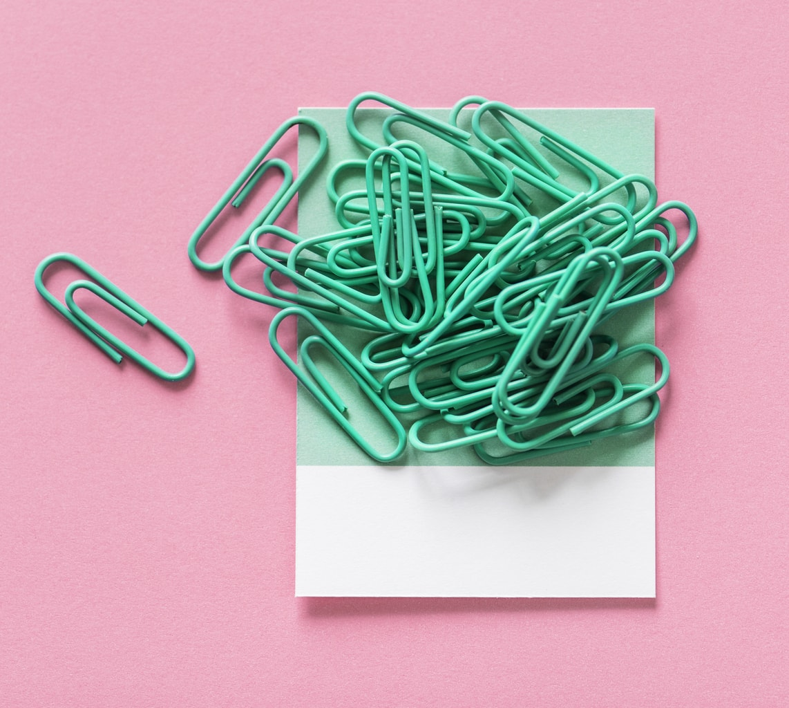 Green paper clips on a pink background