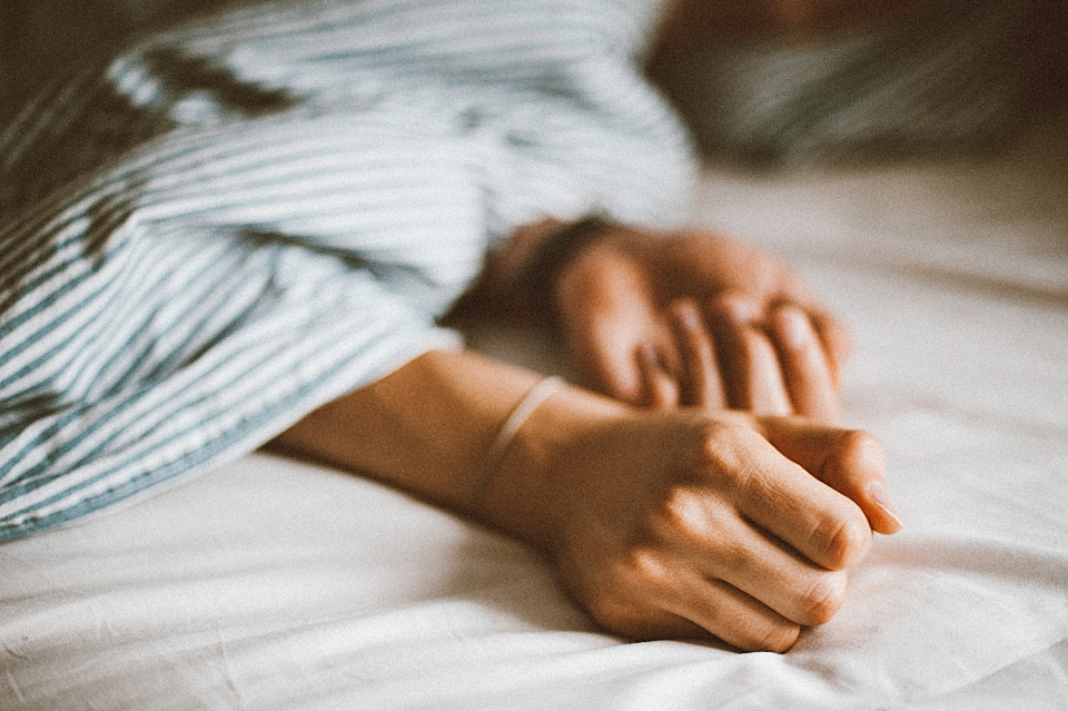 Hands showing in bed under striped comforter