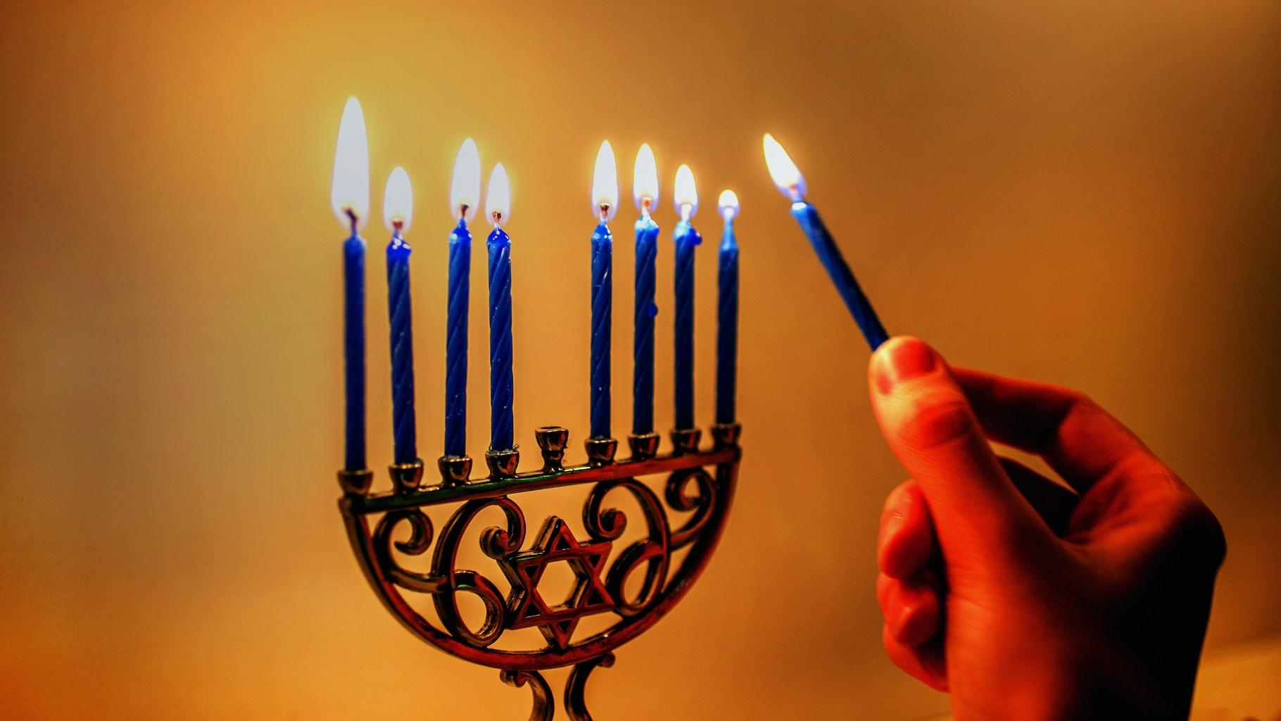 Woman lighting a small Hanukkah menorah with blue candles