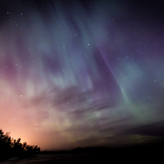 Aurora borealis in the night sky, with the colors pink, green, and purple