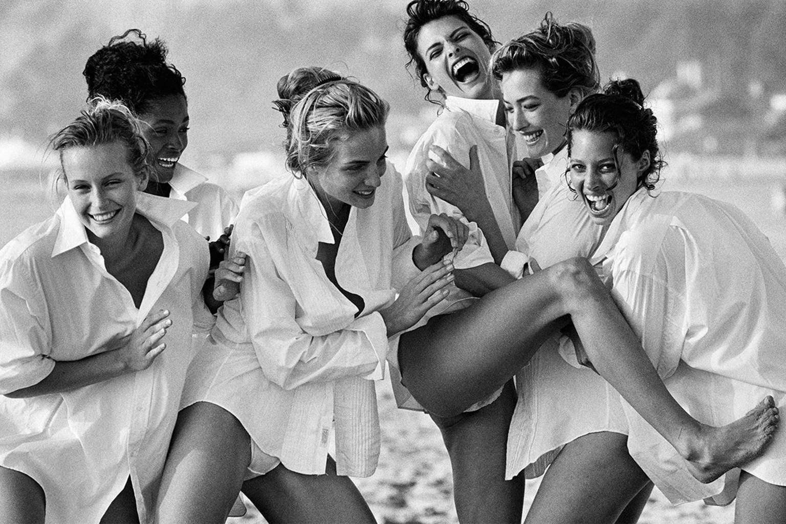 Group of girls laughing in white button-downs.