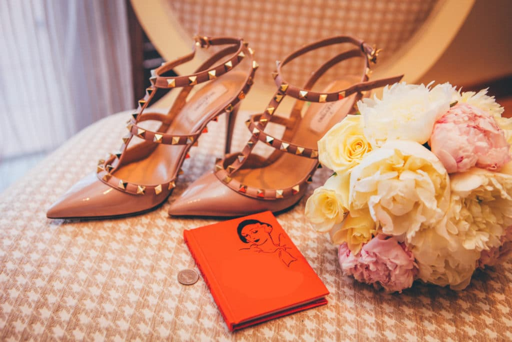 High heels on a table with a bouquet and a journal