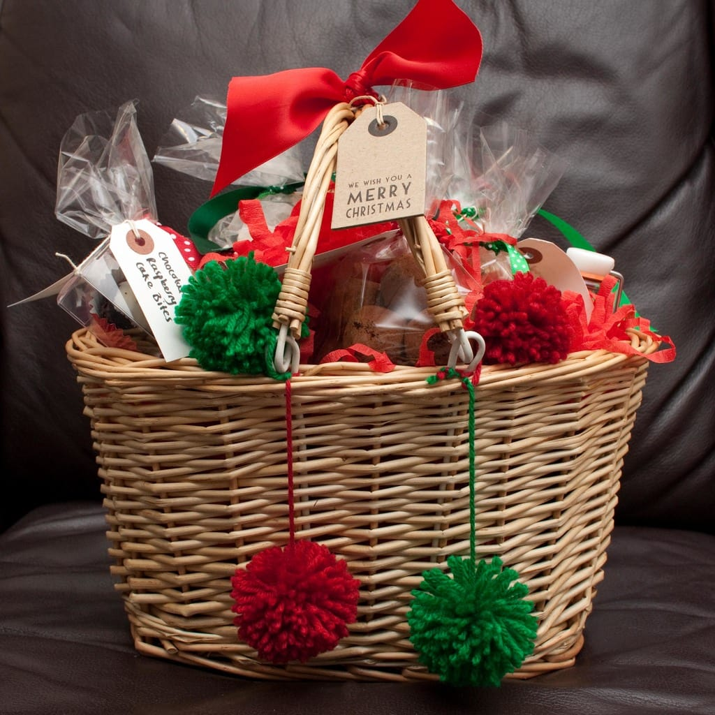 Christmas gift basket with red and green bows and pom poms