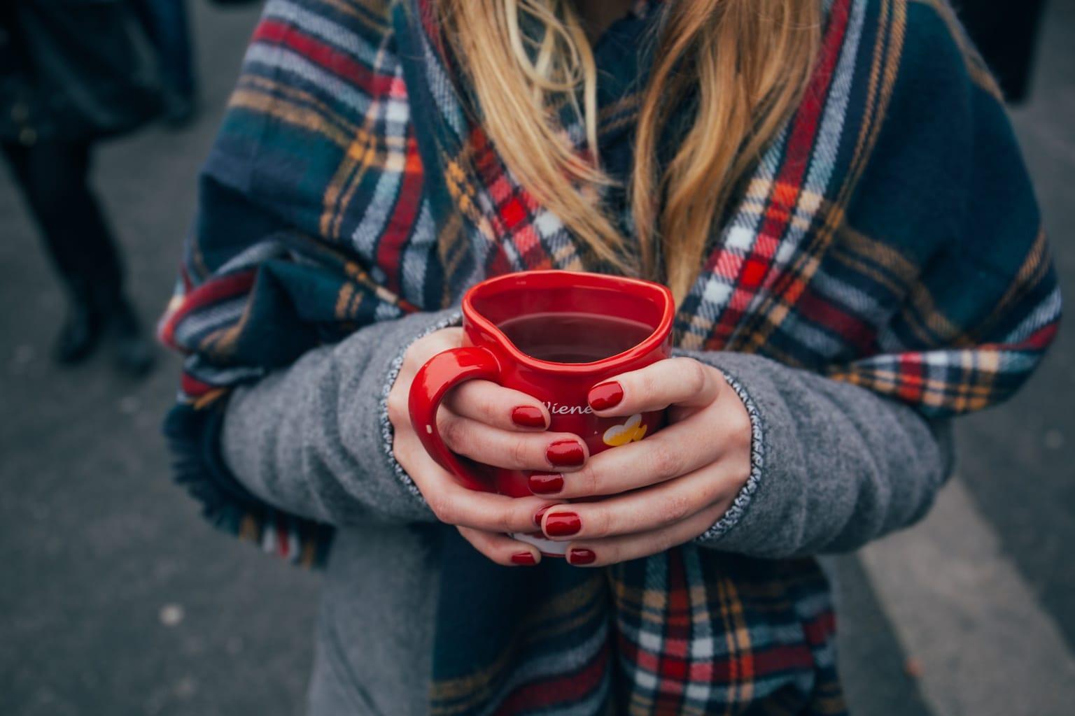 Girl holding a red mug of coffee