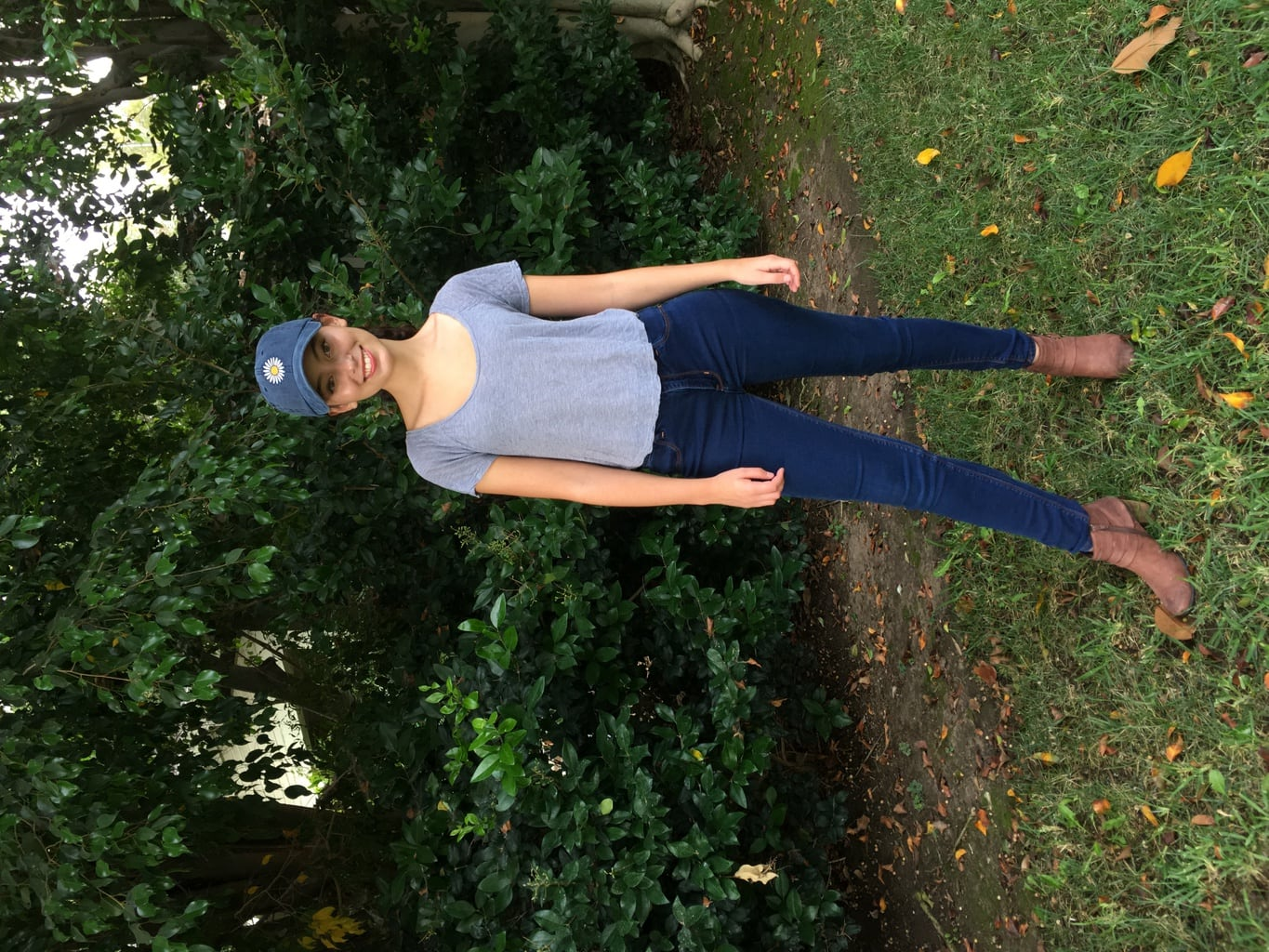 Girl in baseball cap, grey shirt, jeans, and brown boots
