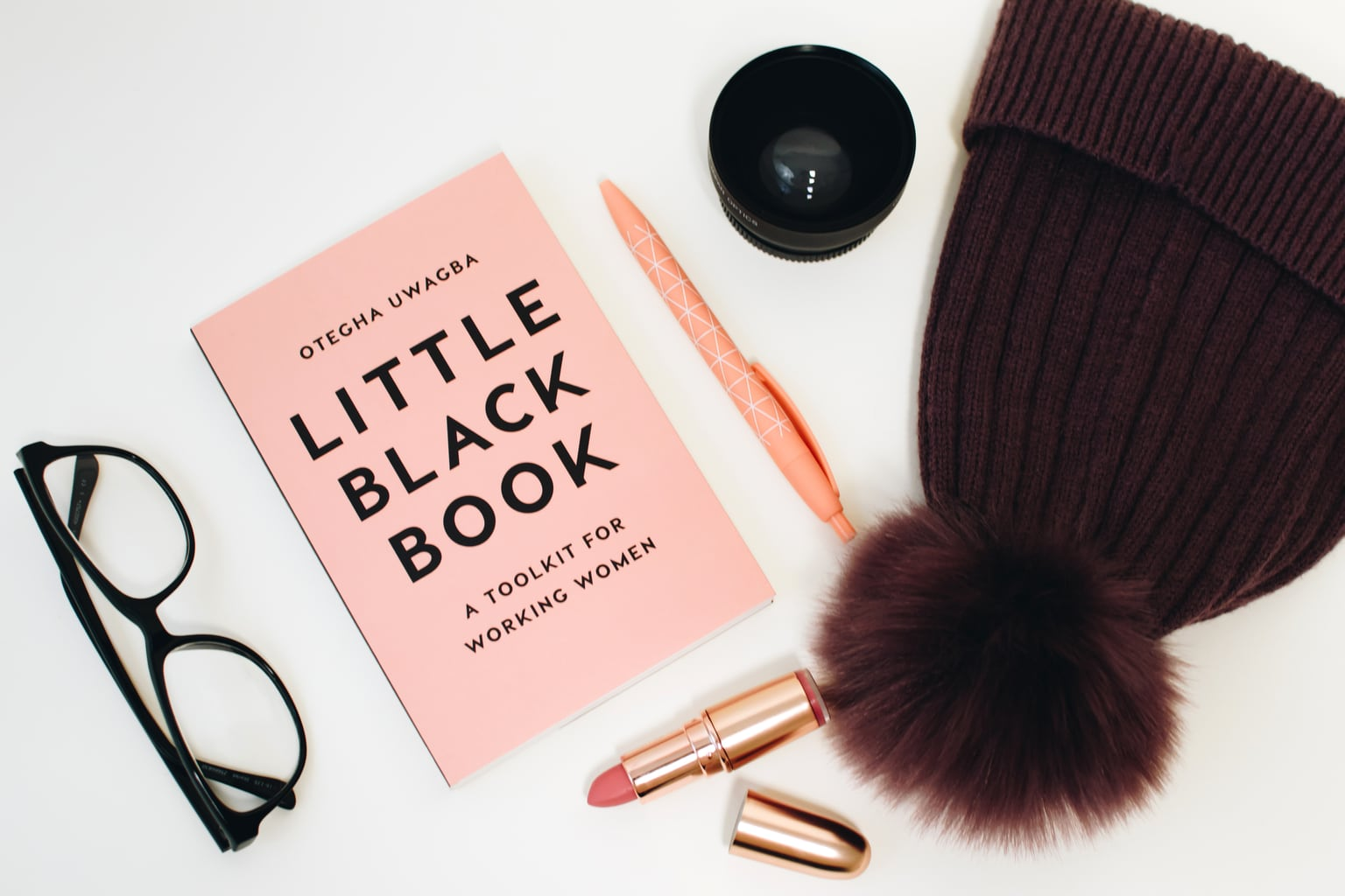 Photo including: glasses, a book, lipstick, a pen, a hat, and a cup.