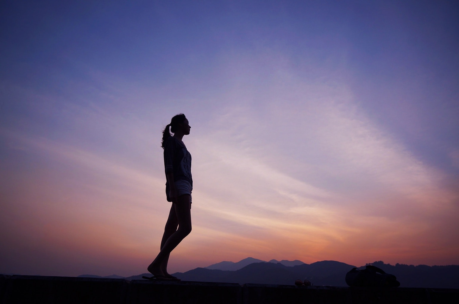 Introverted girl standing alone on a mountain in front of a sunset