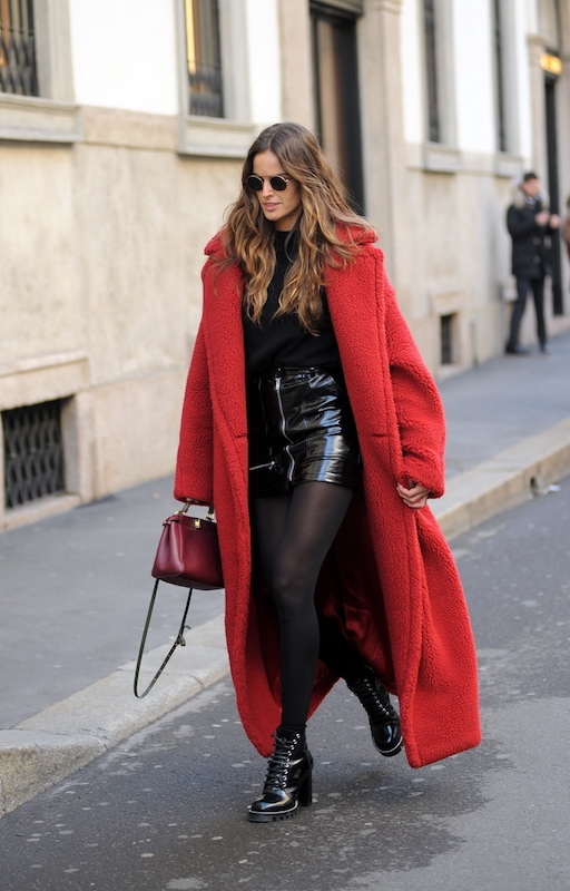 Izabel Goulart wearing a long red teddy bear coat, a black sweater, a black patent leather zipper front mini skirt, a burgundy top-handle mini satchel bag, black tights, and black patent lace-up lug sole booties