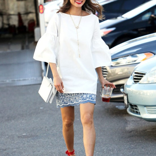 Jamie Chung wearing a bell sleeve top, white bag, red lipstick and red shoes