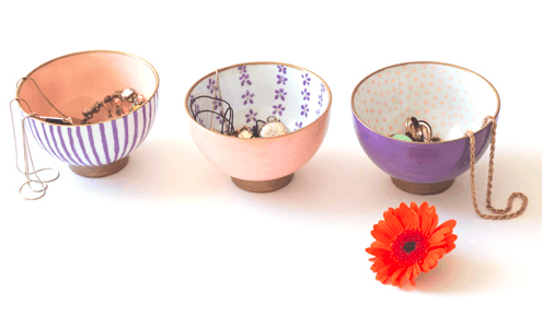 Photo of three printed bowls with jewelry in them and an orange flower in front of them.