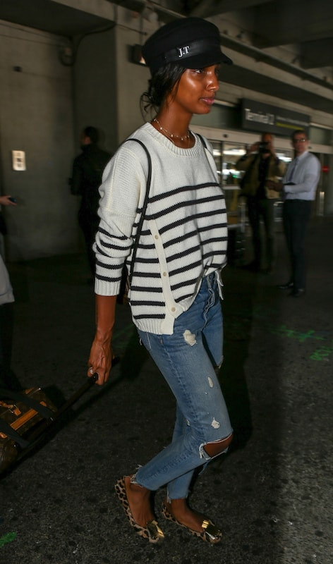 Jasmine Tookes wearing a black cabby hat, a black and white striped sweater, ripped straight leg jeans, and leopard print flats