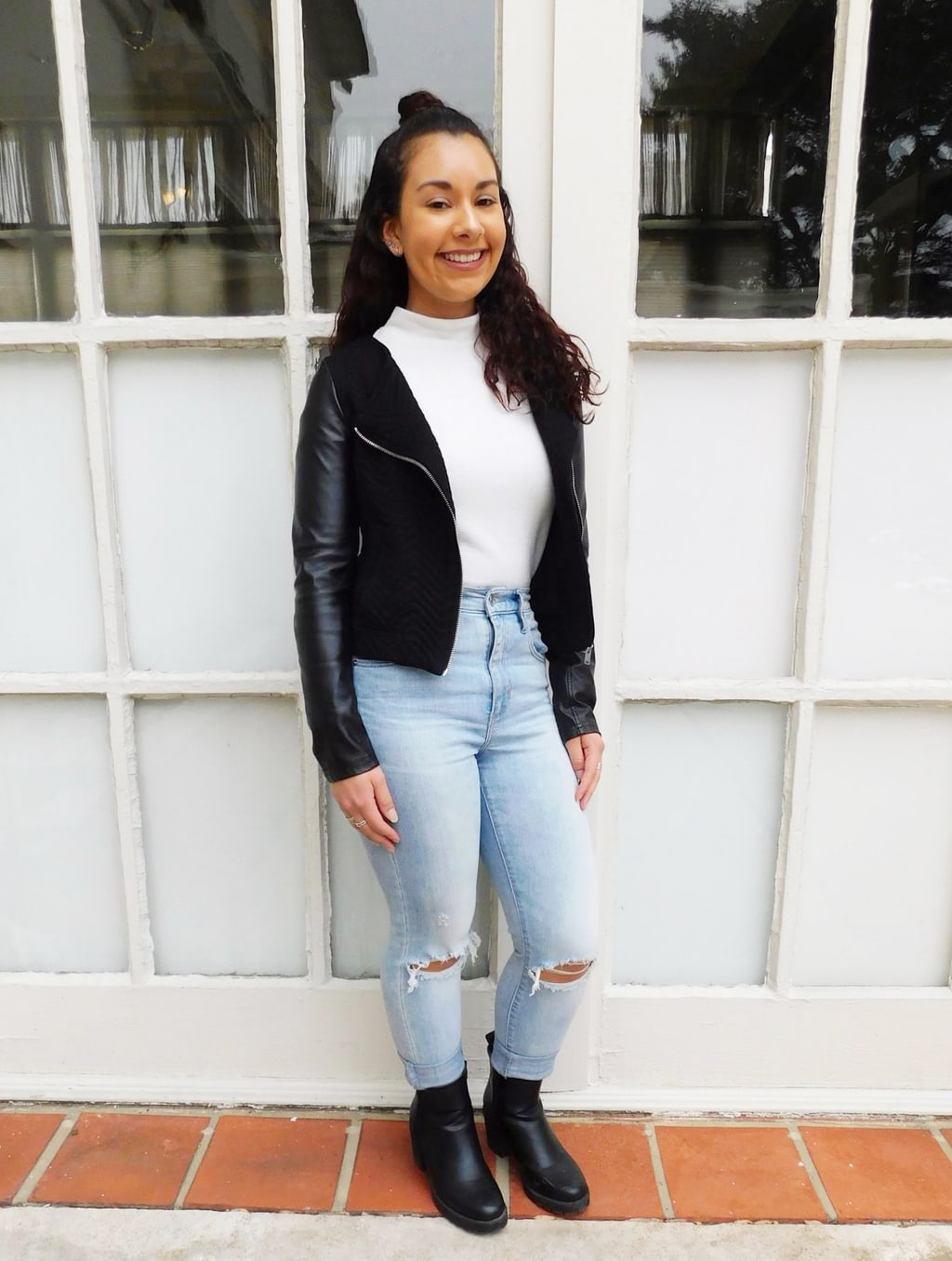 Jefferson University student Jackie styles her simple white turtleneck sweater with a black motorcycle jacket with silver zipper detailing, a pair of high-waisted light-wash denim jeans with distressed knees, and a pair of chunky-heeled booties.