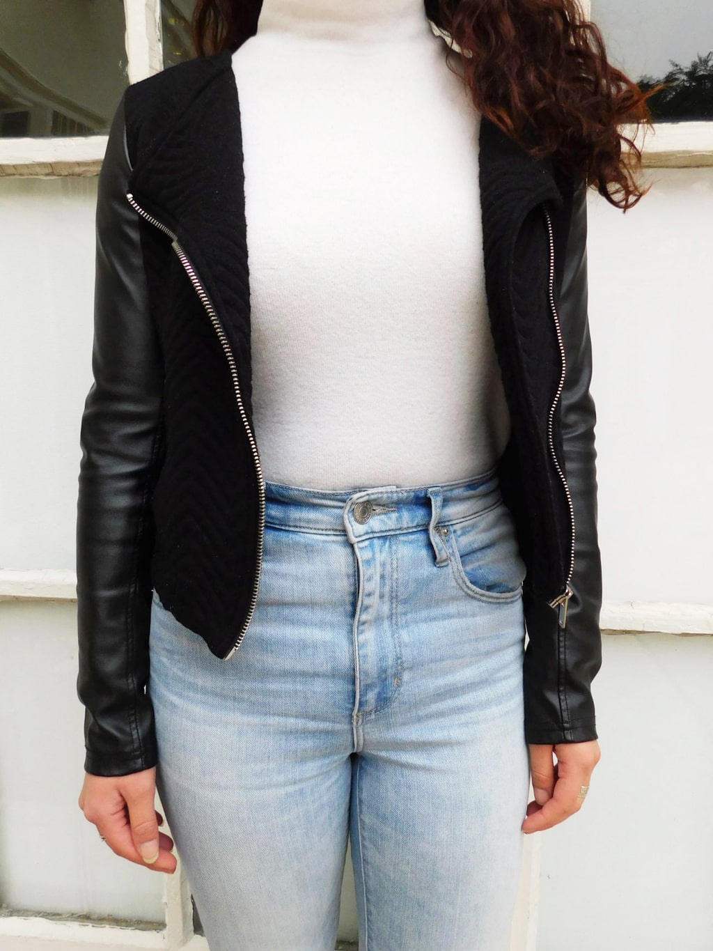Fashion at Jefferson University: This black motorcycle jacket has is a knit material with faux leather sleeves and silver zippers. It is worn here with a white turtleneck and high-waisted denim jeans.